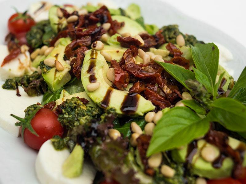 Салат Женевский (моцарела, вяленые помидоры, помидоры черри, салатные листья, кедровые орешки, соус «Песто»)